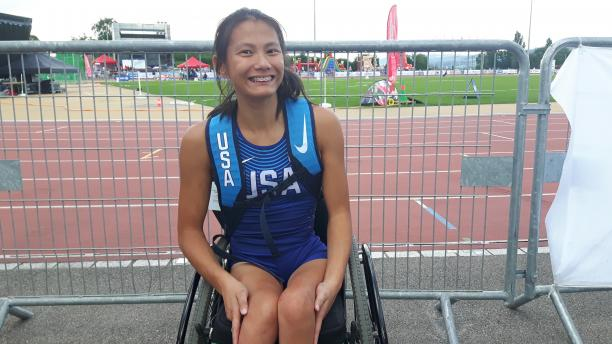 Girl in wheelchair smiles for a photo after her race