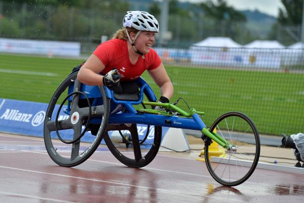 Athlete in a wheelchair celebrates clencing her first with a big smile on a wet track.