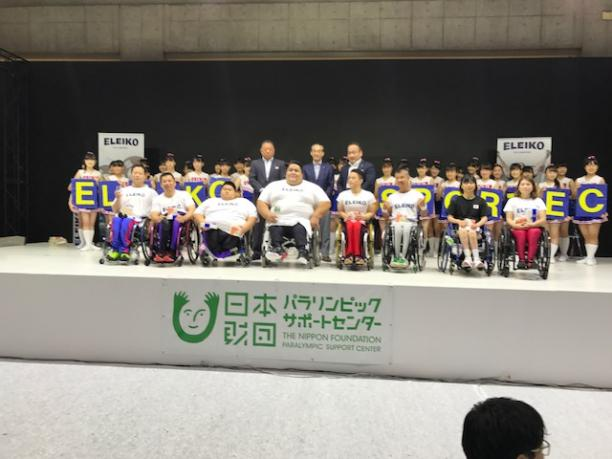 a Para powerlifter on a stage surrounded by young children