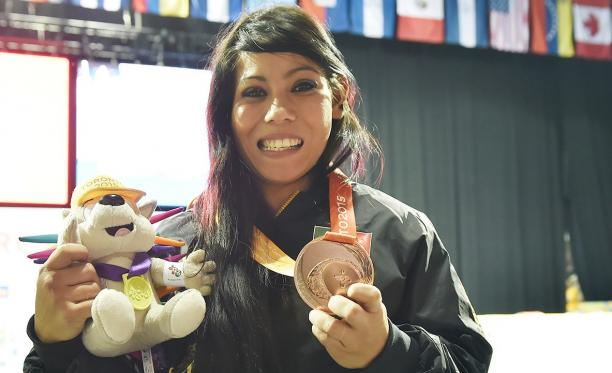 a Para athlete holds her medal and smiles