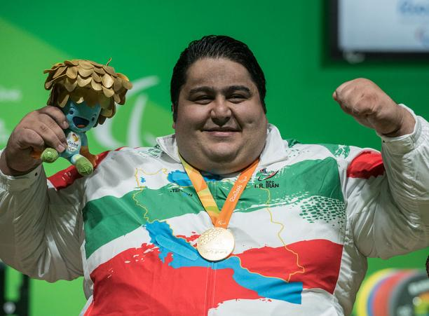 a male Para powerlifter smiles with his medal