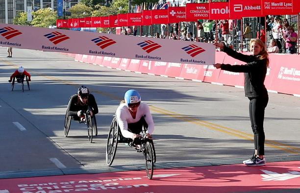 a female wheelchair racer crosses the finish line