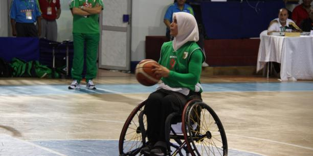 Woman wearing a hijab shooting a basketball in a wheelchair