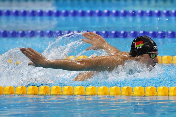 Male swimmer in water competing in butterfly stroke