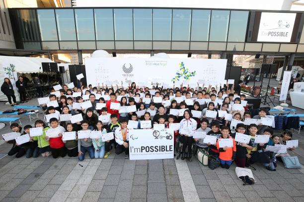 a group of schoolchildren holding up signs