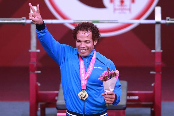 a male powerlifter celebrates his gold medal on the podium