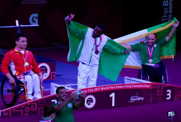 three powerlifters on the podium, two holding up flags