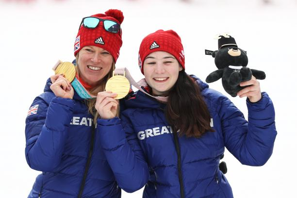 two female alpine skiers with gold medals on the podium
