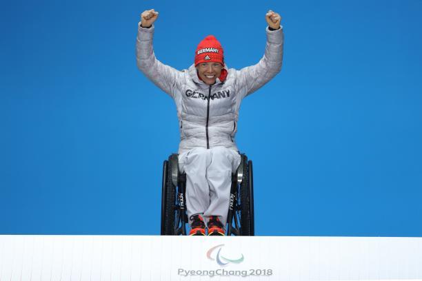 a wheelchair athlete raises her arms on the podium