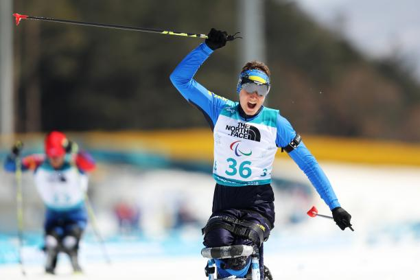 a male Para sit skier crosses the line and celebrates