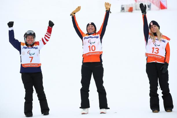 three female snowboarders jump in the air