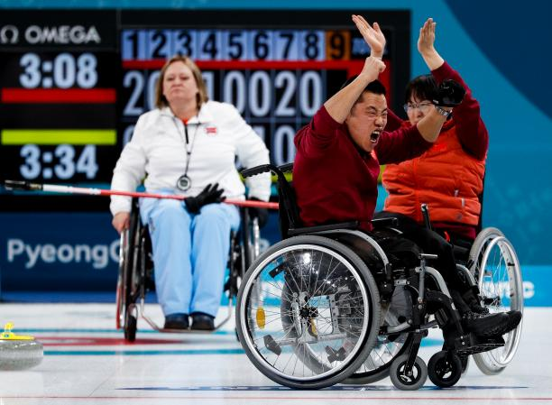 wheelchair curlers celebrating on the ice