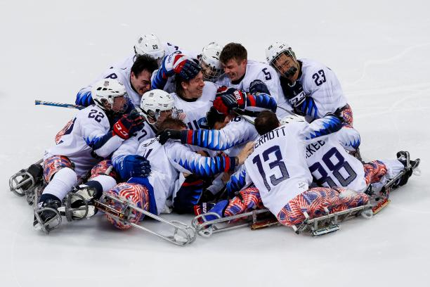 a group of Para ice hockey players in a heap on the ice