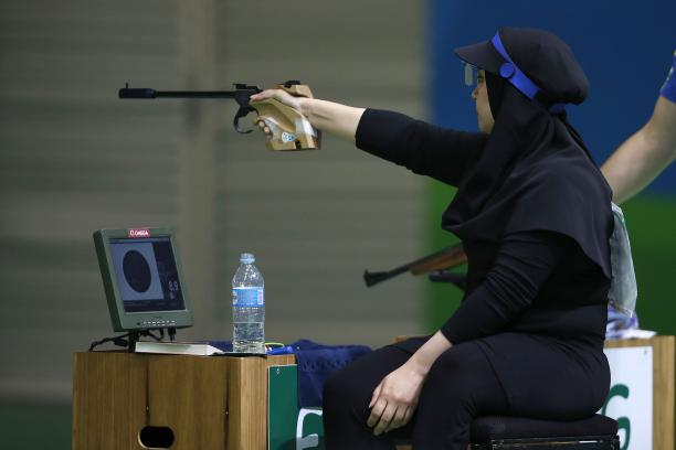 Woman with black headscarf aiming with a weapon