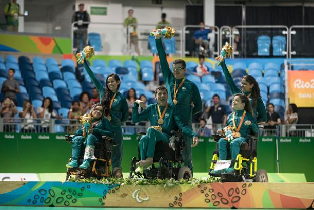 Six people on a podium. Three are in wheelchairs, three are standing behind them