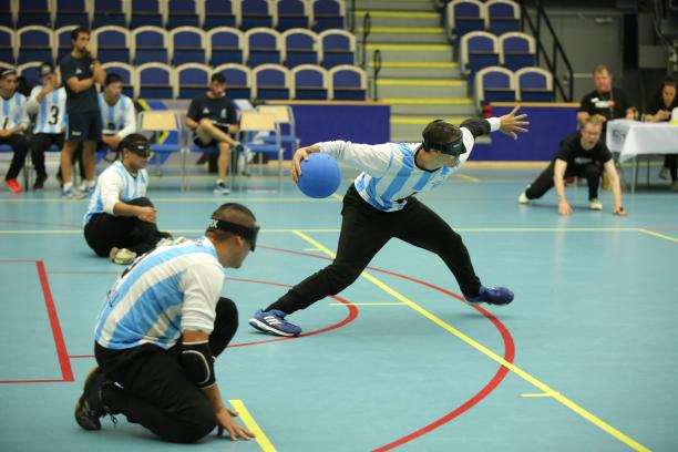 a male goalball player prepares to take a shot while two others wait beside him