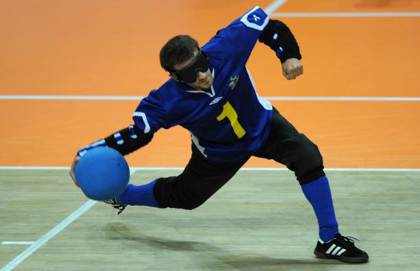 a male goalball player prepares to throw the ball