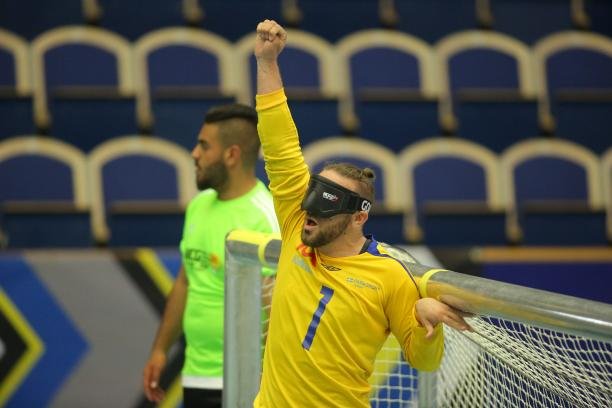 a male goalball player punches the air in celebration