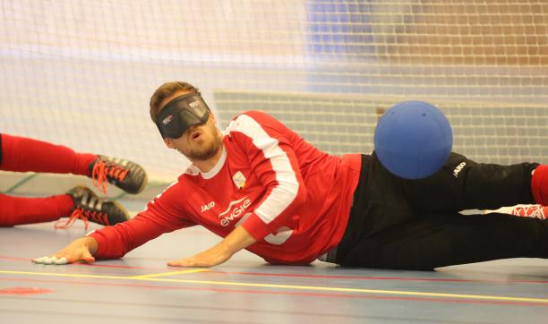 a male goalball player saves a shot