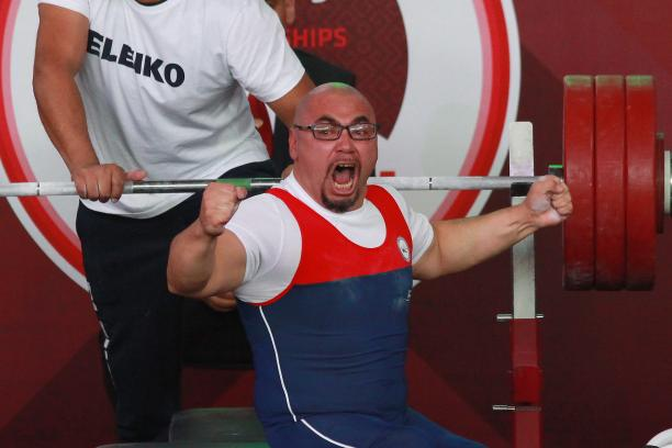 a male powerlifter raises his fists in celebration on the bench