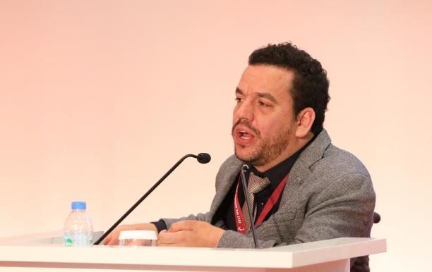 a man speaking into a microphone at a podium