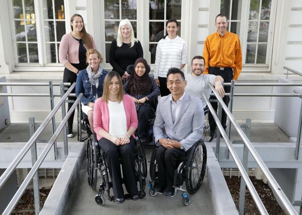 a group of male and female Para athletes sitting and standing outside a white building