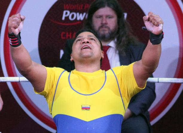a male powerlifter raises his arms in celebration on the bench