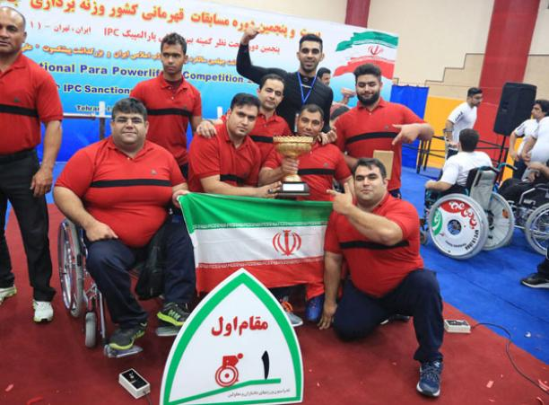 a group of male powerlifters holding an Iran flag and a trophy