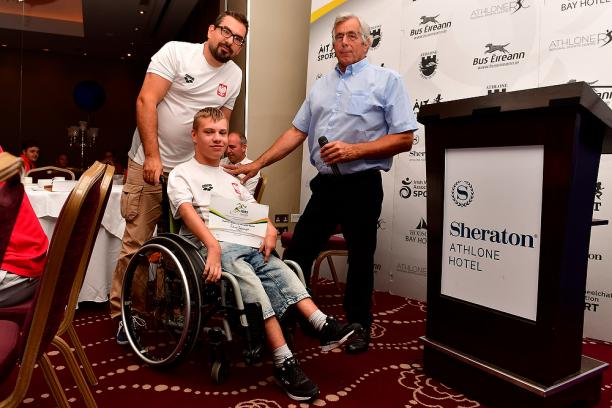 Polish male swimmer Juliusz Trochimczuk in a wheelchair receives an award from two men