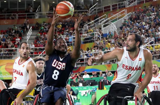 male wheelchair basketball players Alejandro and Pablo Zarzuela challenge a US player for the ball