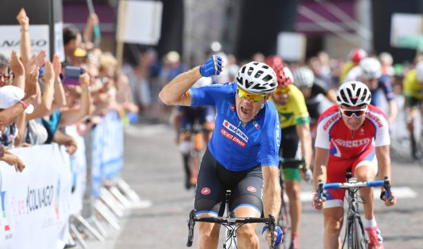male Para cyclist Michele Pittacolo punches the air as he crosses the finish line