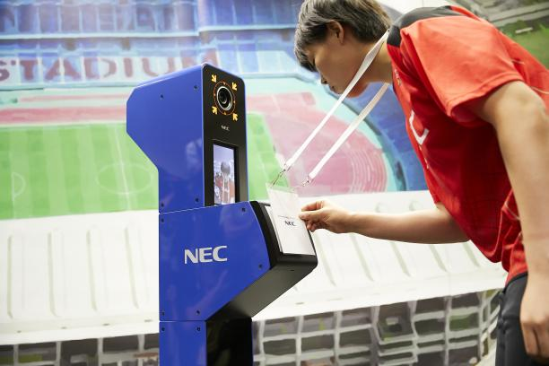 a person looks into a camera while displaying their accreditation in a simulation of the Tokyo 2020 system
