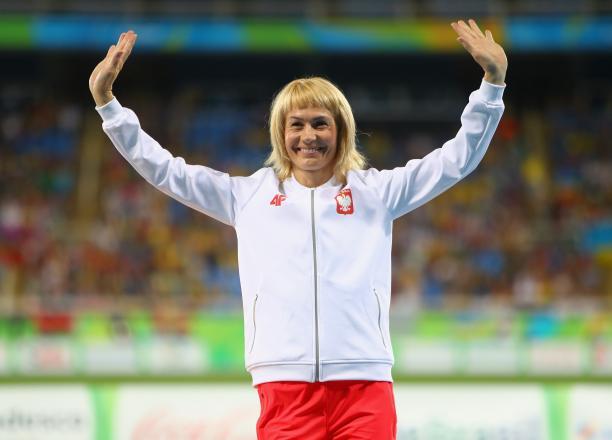 female Para sprinter Barbara Niewiedzial raises her arms on the podium