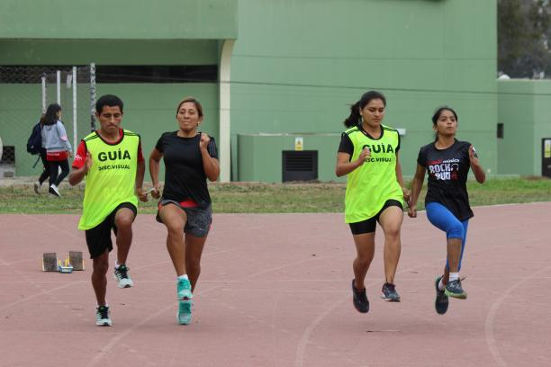 two vision impaired runners competing on the track with their guides
