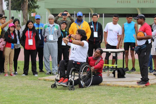 a male wheelchair athlete prepares to throw a shot put
