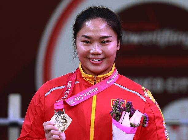 female powerlifter Yujiao Tan holds up her gold medal and a bunch of flowers