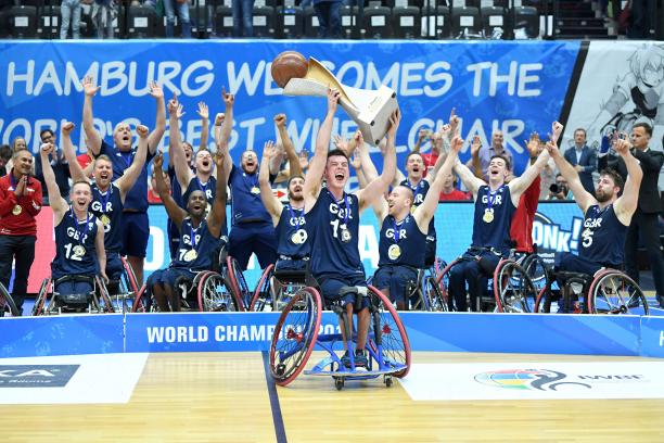 Man in wheelchair hoists basketball trophy with the men's British wheelchair basketball team behind him celerbating