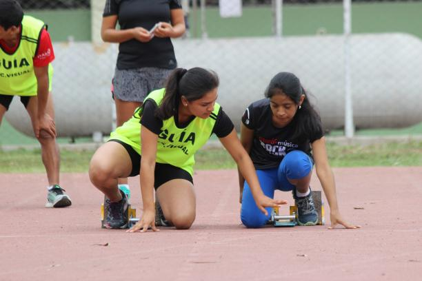 vision impaired runner competing on the track with her guide