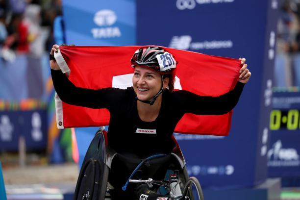 female wheelchair racer Manuela Schaer holds up the Swiss flag