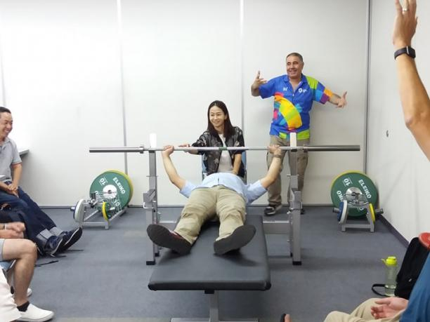an official tries out the weight of a powerlifting bar while lying on the bench