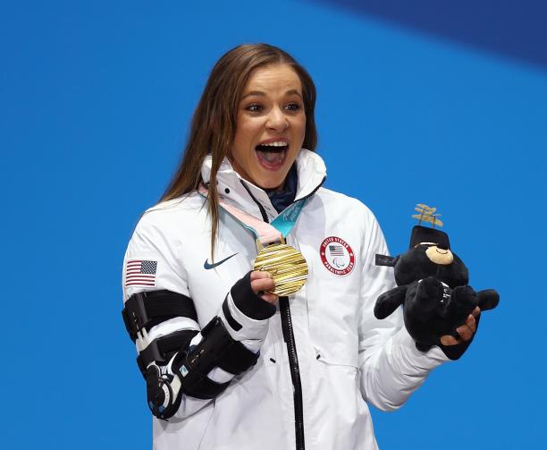 a female Para athlete holds up her gold medal and her mascot