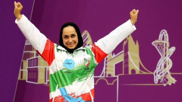 female Para shooter Sareh Javanmardi raises her arms on the podium