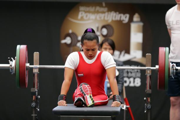 Woman bows head as she sits on powerlifting bench preparing to lift the bar