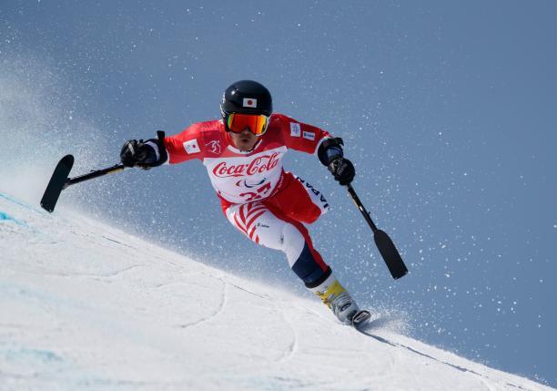 a male Para alpine skier on one leg goes through a gate