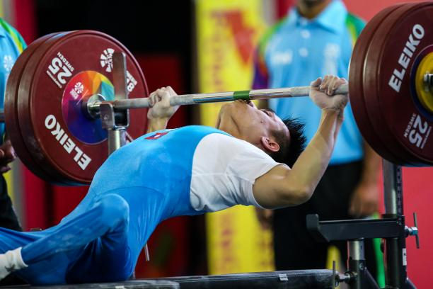 male powerlifter Pia Laophakdee kisses the bar