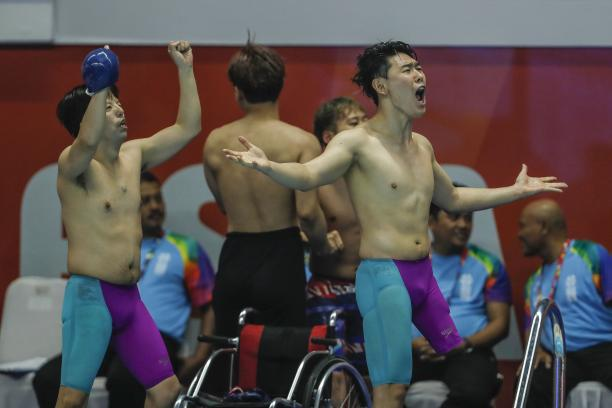 three male Para swimmers celebrate at the edge of the pool
