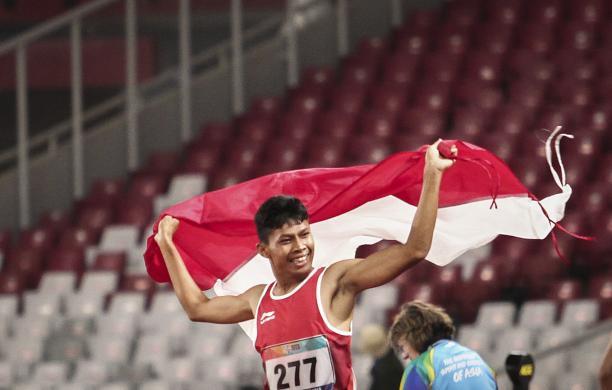 male Para athlete Sapto Yogo Purnomo running holding an Indonesia flag