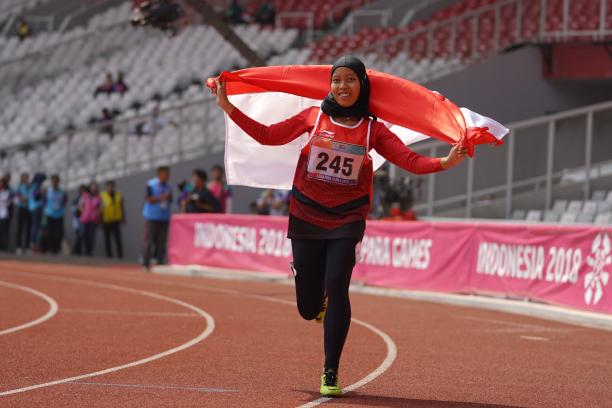 female Para athlete Karisma Tiarani runs down the track holding an Indonesia flag
