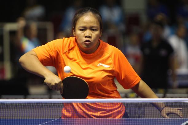 Woman in orange shirt playing table tennis