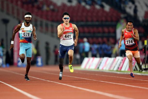 three male sprinters with Shunsuke Itani in the centre run down the 100m track
